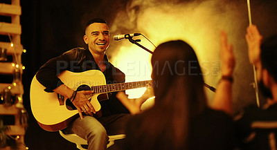 Buy stock photo Cropped shot of a handsome young male musician performing with a guitar in a nightclub