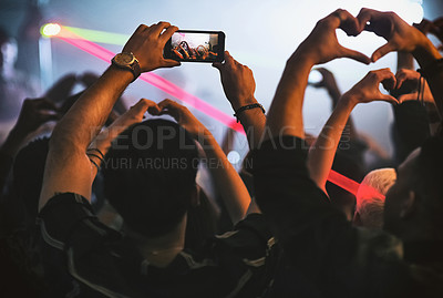 Buy stock photo Rearview shot of a group of unrecognizable young people making the heart shape while standing in a nightclub