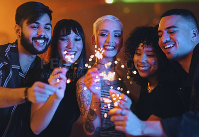 Buy stock photo Cropped shot of a diverse group of young friends having fun with sparklers at a party in a nightclub
