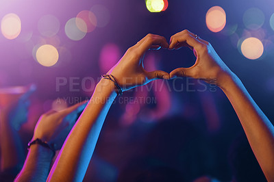 Buy stock photo Cropped shot of an unrecognizable person's hands making a heart shape in a nightclub