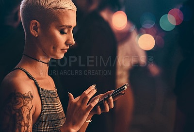 Buy stock photo Cropped shot an attractive young woman using a smartphone while standing in a nightclub