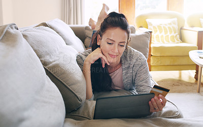 Buy stock photo Full length shot of an attractive young woman looking thoughtful while using a digital tablet and a credit card to shop online in her living room