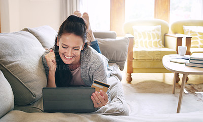Buy stock photo Full length shot of an attractive young woman cheering while holding a digital tablet and a credit card on her couch at home