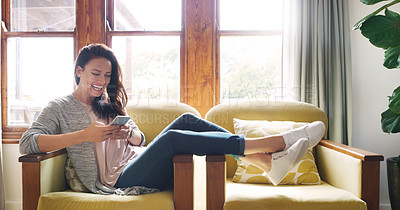 Buy stock photo Full length shot of an attractive young woman laughing while using a smartphone on her couch at home