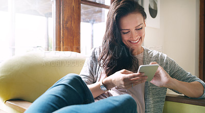 Buy stock photo Cropped shot of an attractive young woman smiling while using a smartphone on her couch at home
