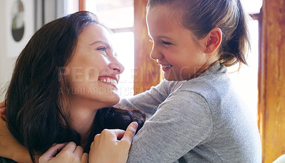 Buy stock photo Cropped shot of an affectionate young mother smiling at her daughter while spending time with her at home