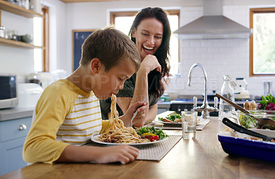 Buy stock photo Cropped shot of an affectionate young boy going in on his spaghetti while his mother laughs in the background