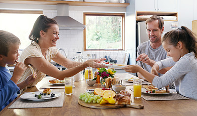 Buy stock photo Cropped shot of two affectionate young parents having breakfast with their  kids in the kitchen at home