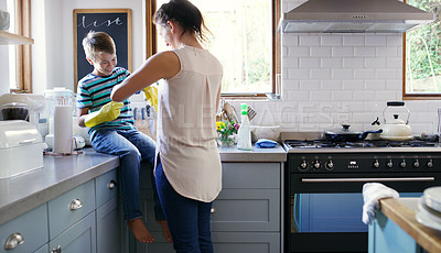 Buy stock photo Cropped shot of an affectionate young mother helping her son to put on rubber gloves while preparing to clean their kitchen