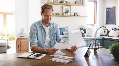 Buy stock photo Cropped shot of a handsome young man looking cheerful while going through his budget at home