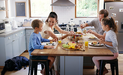 Buy stock photo Cropped shot of two affectionate young parents having breakfast with their two kids in their kitchen at home