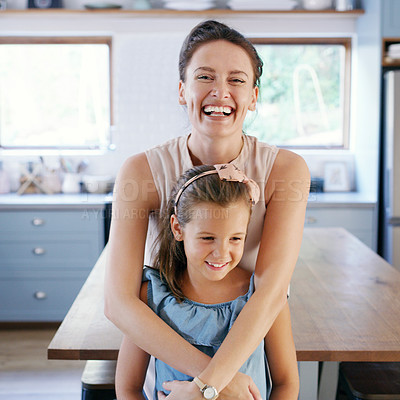 Buy stock photo Cropped shot of an affectionate young mother looking cheerful while holding her daughter in their kitchen at home