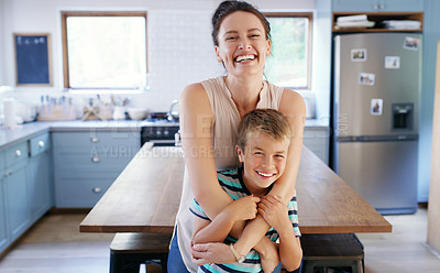 Buy stock photo Cropped portrait of an affectionate young mother looking ecstatic while holding her son in their kitchen at home