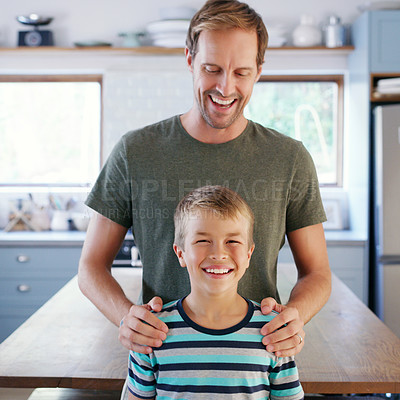 Buy stock photo Cropped shot of an affectionate young father looking cheerful while standing with his son in their kitchen at home