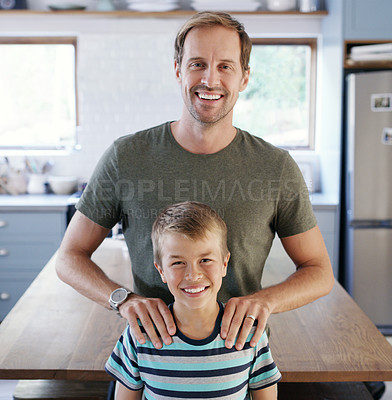 Buy stock photo Cropped portrait of an affectionate young father looking cheerful while standing with his son in their kitchen at home