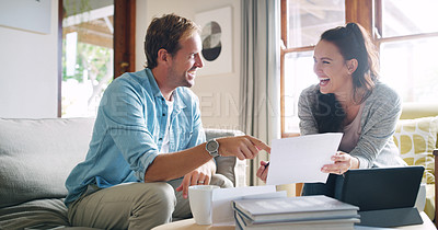 Buy stock photo Cropped shot of an affectionate young couple laughing together while going through their budget at home