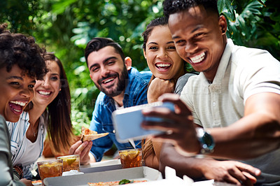 Buy stock photo Shot of a young group of friends enjoying themselves and taking selfies with a cellphone at an outdoor cafe