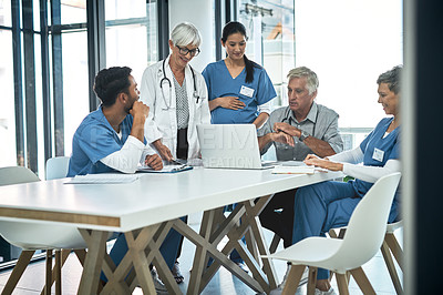 Buy stock photo Shot of a group of medical practitioners working together on a laptop in a hospital boardroom