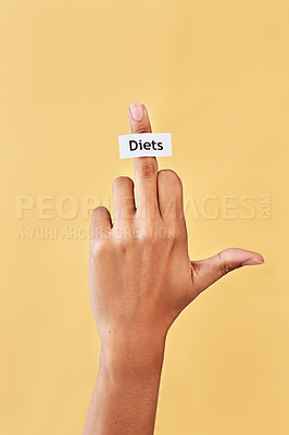 Buy stock photo Studio shot of an unrecognizable woman's hand showing the middle finger while a note that has the word