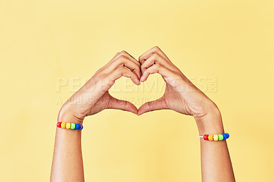 Buy stock photo Studio shot of an unrecognizable woman's hands making a heart shape while she's wearing rainbow bracelets