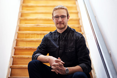Buy stock photo Cropped portrait of a handsome young businessman sitting alone on the wooden staircase in his office