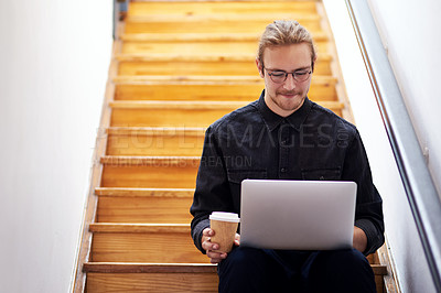 Buy stock photo Cropped shot of a handsome young businessman sitting alone on the staircase alone and using his laptop