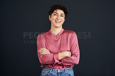 Buy stock photo Cropped portrait of an attractive young businesswoman standing alone with her arms folded against a black background in the studio