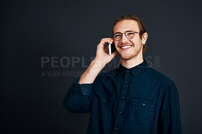 Buy stock photo Cropped shot of a handsome young businessman standing and talking on his cellphone against a black background in the studio