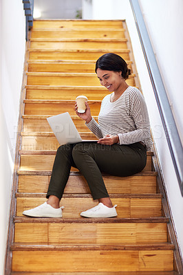 Buy stock photo Full length shot of an attractive young businesswoman sitting on a wooden staircase and using her laptop while holding coffee