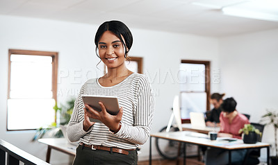 Buy stock photo Cropped portrait of an attractive young businesswoman using a tablet while her colleagues work behind her in the office