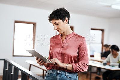 Buy stock photo Cropped shot of an attractive young businesswoman using a tablet while her colleagues work behind her in the office