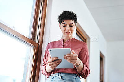 Buy stock photo Cropped shot of an attractive young businesswoman standing and using a tablet in her office alone