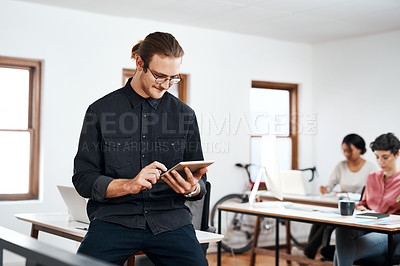 Buy stock photo Cropped shot of a handsome young businessman using a tablet while his colleagues work behind him in the office