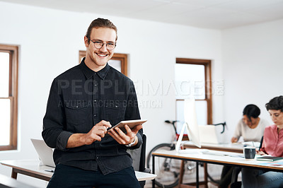 Buy stock photo Cropped portrait of a handsome young businessman using a tablet while his colleagues work behind him in the office