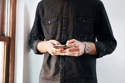 Buy stock photo Cropped shot of an unrecognizable businessman standing alone in his office and texting on his cellphone