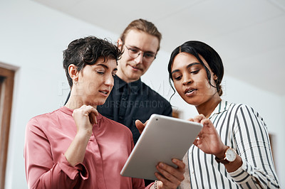 Buy stock photo Cropped shot of a diverse group of businesspeople standing together and using a tablet in the office