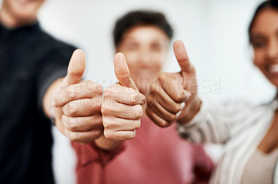 Buy stock photo Cropped portrait of a diverse group of businesspeople standing together and making a thumbs up gesture in the office