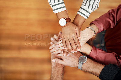 Buy stock photo Cropped shot of an unrecognizable group of businesspeople standing with their hands together in celebration in the office