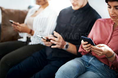 Buy stock photo Cropped shot of a diverse group of businesspeople sitting in the office together and texting on their cellphones
