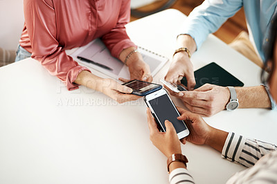 Buy stock photo Cropped shot of an unrecognizable group of businesspeople sitting together and using their cellphones during a meeting