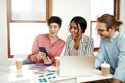 Buy stock photo Cropped shot of a diverse group of businesspeople sitting together and using technology during a meeting in the office