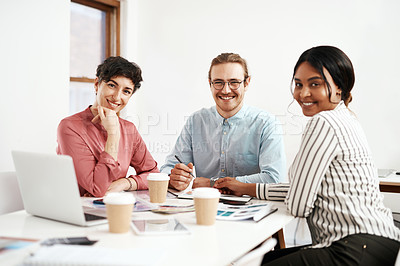 Buy stock photo Cropped portrait of a diverse group of businesspeople sitting together and smiling during a successful meeting in the office