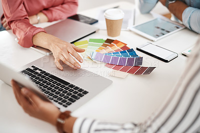 Buy stock photo Cropped shot of an unrecognizable group of businesspeople sitting together and working with colour schemes on a laptop