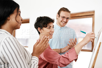 Buy stock photo Cropped shot of an attractive young businesswoman standing and writing on a white board while her colleagues clap for her