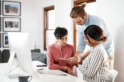 Buy stock photo Cropped shot of a diverse group of businesspeople working on a tablet together during a meeting in the office