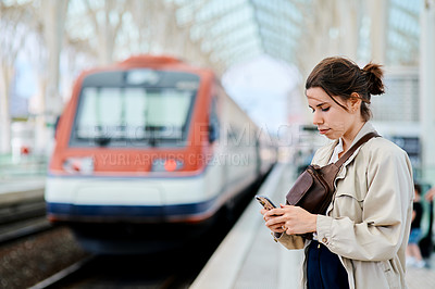 Buy stock photo Cropped shot of an attractive young woman standing and using her cellphone while waiting for her train in the station
