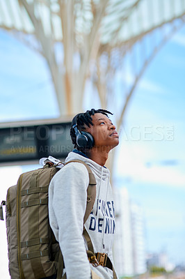 Buy stock photo Cropped shot of a handsome young man standing alone and listening to music through headphones while waiting for his train
