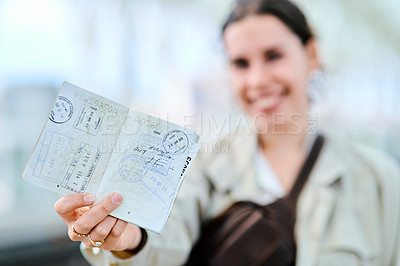 Buy stock photo Cropped portrait of an attractive young woman standing and showing her passport while waiting for her train at the station