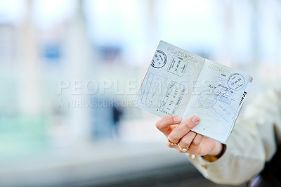 Buy stock photo Cropped shot of an unrecognizable young woman standing and showing her passport while waiting for her train at the station