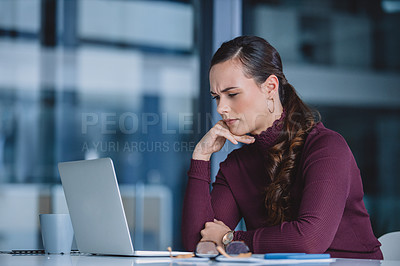 Buy stock photo Cropped shot of an attractive young businesswoman looking contemplative while sitting alone in her office and using her laptop